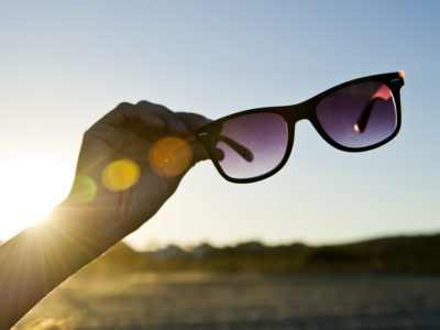 Hand Holding Black Sunglasses at sunset in front of vibrant blue sky. The Sun iluminates de scene with the golden light of dawning. Backlit